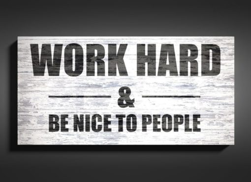 "Tablica motywacyjna z cytatem po angielsku ""Work hard and be nice to people""."