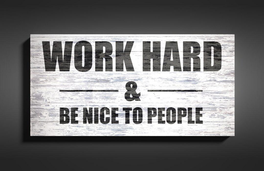 """Tablica motywacyjna z cytatem po angielsku """"Work hard and be nice to people""""."""