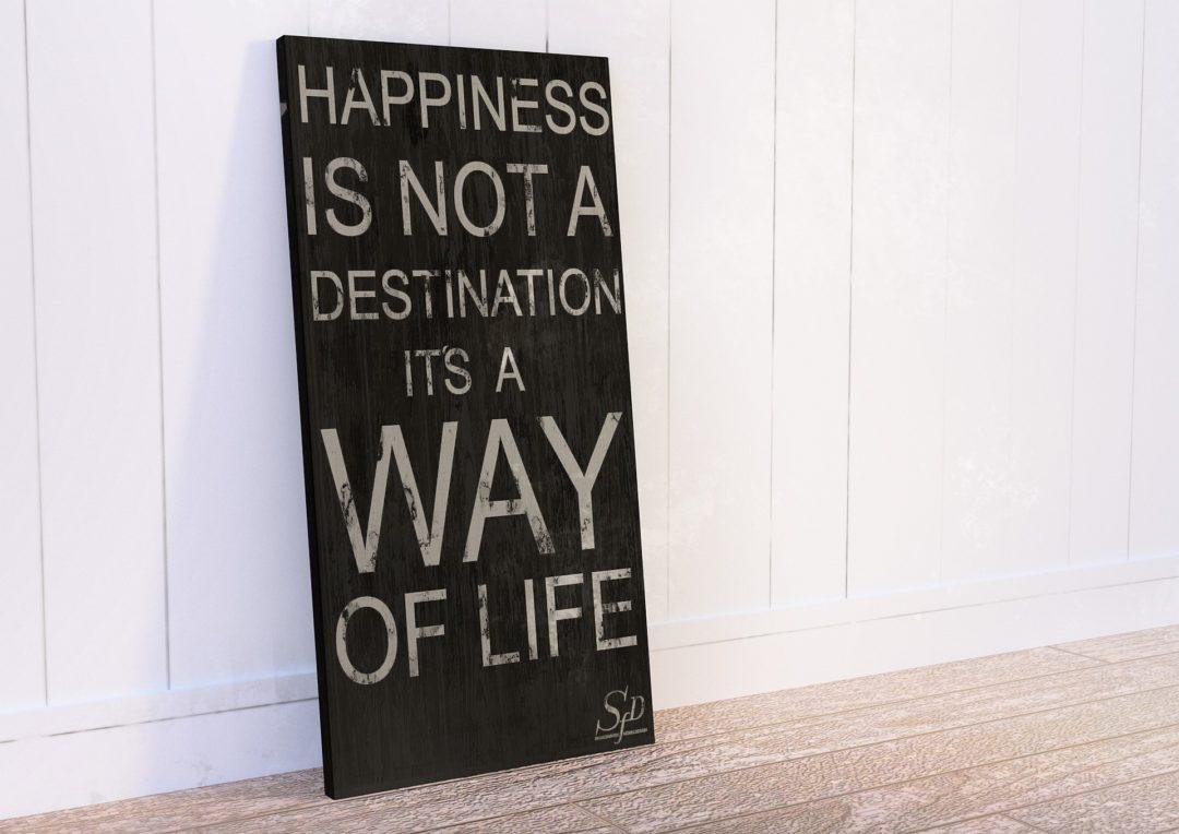 """Drewniana tablica z cytatem """"Happiness is not a destination it's a way of life"""". Jest to optymistyczne przesłanie oznaczające: szczęście to nie cel ale droga."""