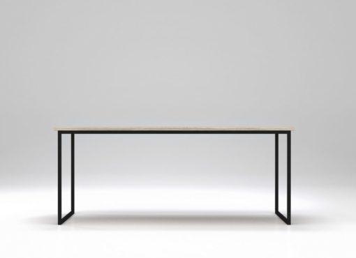 Stół minimalistyczny Basic Fyra. Widok na dłuższy bok stołu. Prosta, biała linia dębowego blatu oparta na stalowej, czarnej ramie. Biały kolor blatu nie tworzy jednolitej warstwy, dzięki czemu widoczny jest delikatny rysunek drewna. Drewno jest delikatnie strukturyzowane. Stół minimalistyczny Basic Fyra produkowany jest ręcznie, zgodnie ze sztuką rzemieślniczą. Jego rama wykonana jest ze stali i malowana na kolor czarny. Pod ręką można wyczuć delikatną, matową teksturę.