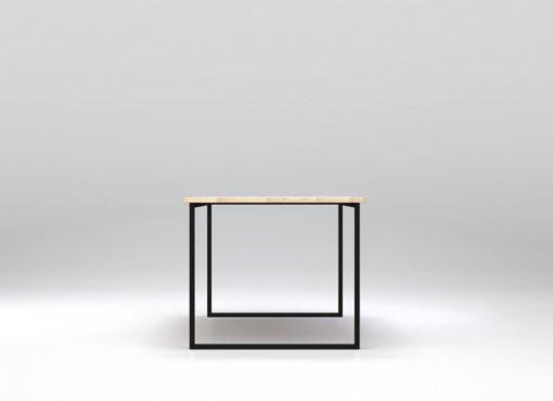 Minimalistyczny stół Basic Fyra. Widok na krótszy bok stołu. Biały blat stołu Basic Fyra zestawiony z czarną, stalową ramą. Widoczne słoje poprzeczne na krawędzi blatu. Drewno jest delikatnie strukturyzowane. Stół minimalistyczny Basic Fyra produkowany jest ręcznie, zgodnie ze sztuką rzemieślniczą.