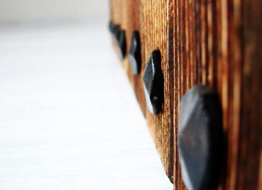 Drewniane ściany połączone są za pomocą ręcznie kutych, stalowych gwoździ, których zwieńczenia, widoczna na krótszych bokach, pełnią dodatkowo elementem ozdobnym.