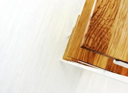 Półka drabinka SMUKKE. Pięć kwadratowych półek, ustawionych jedna nad drugą, jest wykonanych z litego drewna dębowego. Ciepły kolor drewna nadaje wnętrzu przyjemnego tonu.