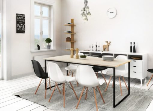"""Minimalistyczny stół Basic Fyra w jadalni w skandynawskim stylu. Stół wraz z sześcioma krzesłami zajmuje centralną część jadalni. Na ścianie widoczna tablica z napisem """"Happiness it is not a destination it is way of life"""". Stół Basic Fyra wykonywany jest ręcznie. Składa się z dwóch elementów: blatu oraz stalowej ramy. Blat wykonany jest z wyselekcjonowanego drewna dębowego. W procesie produkcji jest on starannie obrabiany, strukturyzowany oraz bielony naturalnymi olejami do drewna. Rama zaprojektowana została w postaci wstążki tworzącej kształt litery U. Brak wspornika biegnącego przy podłodze. Jasny blat idealnie komponuje się z wnętrzami o różnym charakterze. Tu przedstawiony we wnętrzu w skandynawskim stylu."""